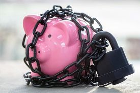 Piggy bank savings secured with padlock chained up and locked