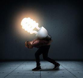 Young Man Carry A Big Lightbulb . Having A Good Idea Concept .