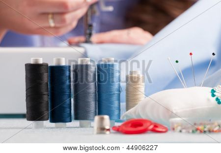 reels of colour threads and other sewing accessories like pins, buttons and thimble with woman's hands using sewing machine