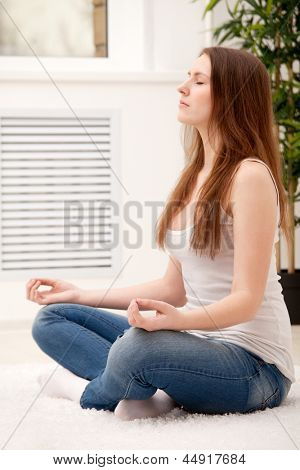 Woman sitting on Floor zu Hause tun Yoga meditation