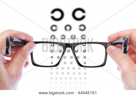 Glasses In The Hands Of Men. Checking Vision The Table Golovin.