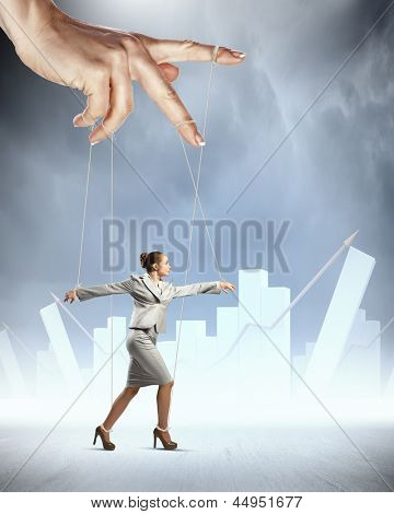 Businesswoman marionette on ropes controlled by puppeteer against bars background