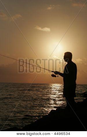 Man Fishing At Sunset On The Gulfcoast