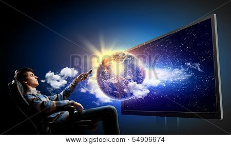 Young man in armchair with click watching TV