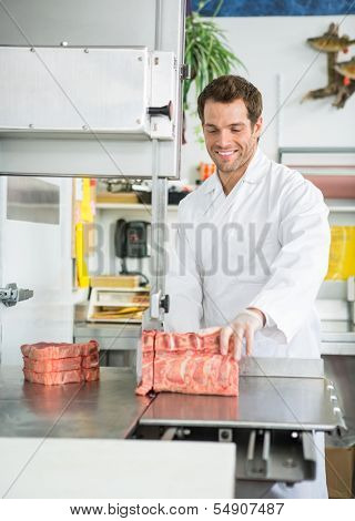 Happy young male butcher cutting meat on bandsaw at store
