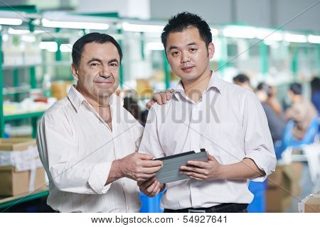 caucasian businessman manager and male chinese worker man in china factory manufacturing production