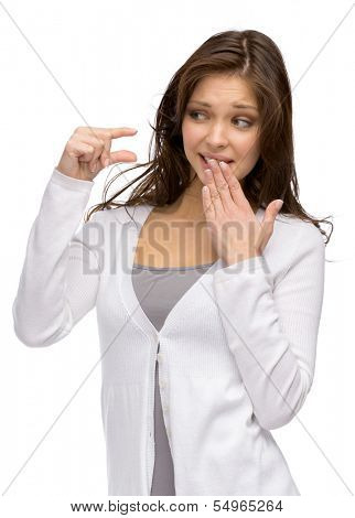 Half-length portrait of woman showing small amount of something and covering mouth with a hand, isolated on white
