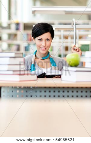Female student with green apple studies sitting at the desk at the reading hall of the library. Information concept