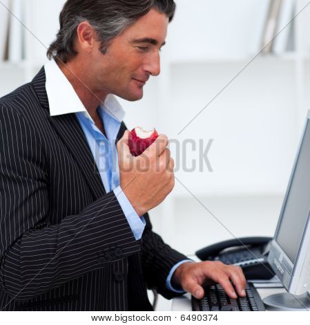 Close-up Of A Happy Businessman Eating A Red Apple