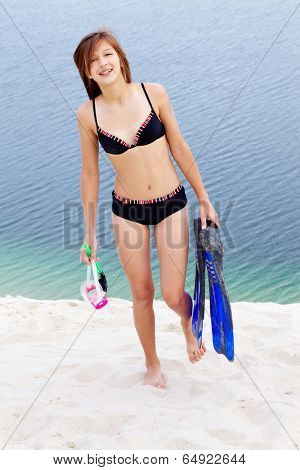 Portrait of teenage girl in bikini carrying scubadiving equipment