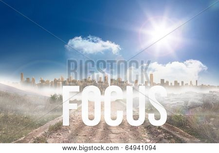 The word focus against stony path leading to large urban sprawl under the sun