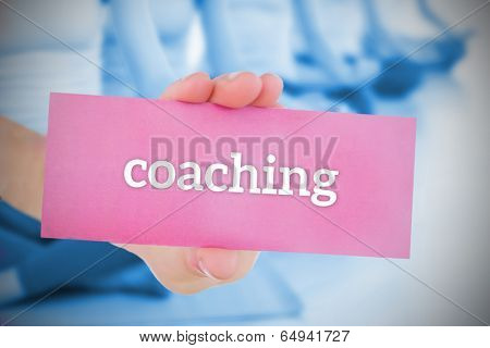 Woman holding pink card saying coaching against yoga class in gym
