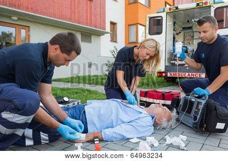 Paramedics giving firstaid to unconscious senior patient lying on ground