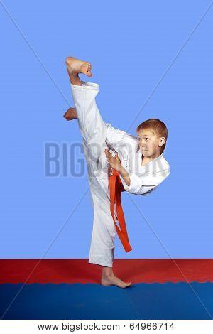 Training strike yoko-geri athlete in white karategi