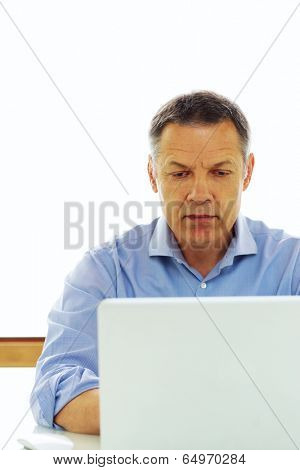 Portrait of a middle aged caucasian man looking at his laptop computer.