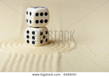 Two White Dice With Black Dots On Sand