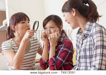 Asian women use a magnifier to find the shortcoming on her friend.