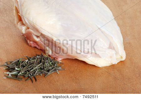 raw chicken breast with fresh rosemary