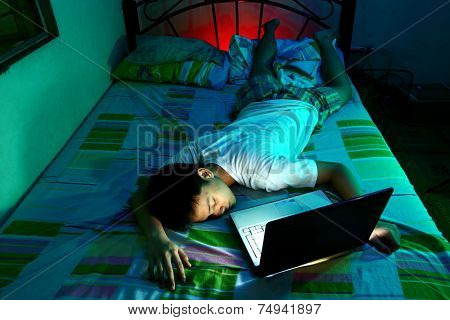 Young Teen sleeping front of a laptop computer and on a bed