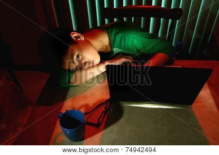 Young Teen resting in front of a laptop computer