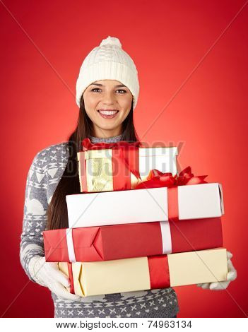 Portrait of lovely girl in winterwear holding wrapped gifts