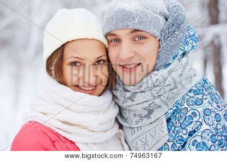 Smiling girlfriend and boyfriend in winterwear looking at camera