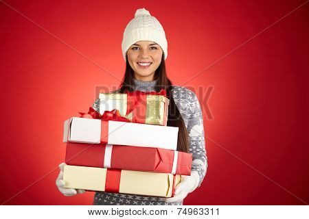 Portrait of happy girl in winterwear holding stack of giftboxes over red background