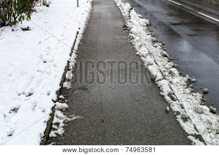 snow on sidewalk and street, symbol for accident risk and photo r���¤umpflicht