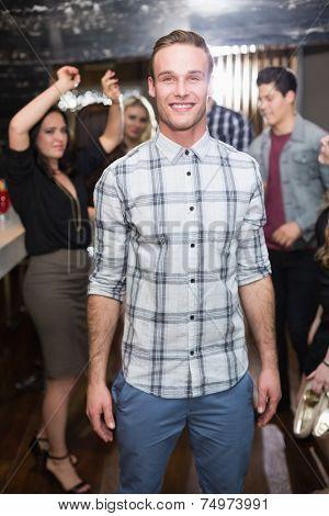 Stylish man smiling on the dancefloor at the bar
