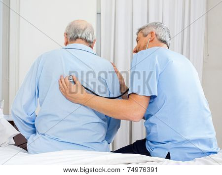 Male caretaker examining senior man's back with stethoscope in bedroom at nursing home