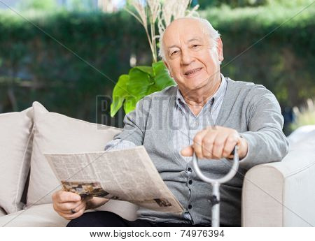 Portrait of confident senior man with newspaper and walking stick sitting on couch at nursing home porch
