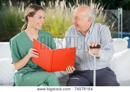 Smiling female nurse and senior man looking at each other while reading book at nursing home
