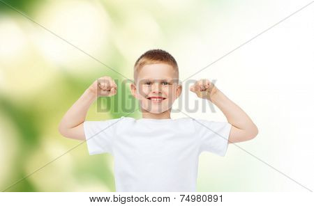 advertising, ecology, people and childhood concept - smiling little boy in white blank t-shirt flexing biceps over green background