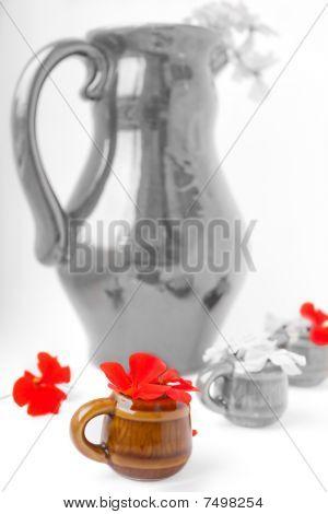 The big jug with geranium and mugs