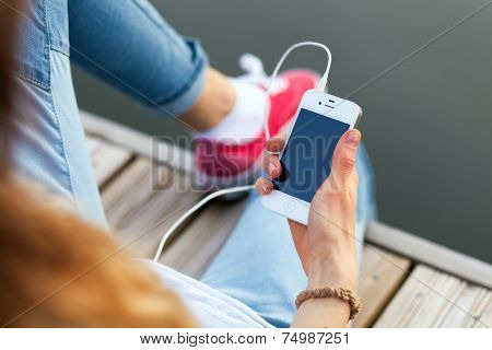 WROCLAW, POLAND - OCTOBER 12, 2014: Teenager sitting on a pier holding an Apple iPhone smartphone