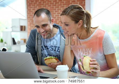 Roommates eating sandwich in front of laptop