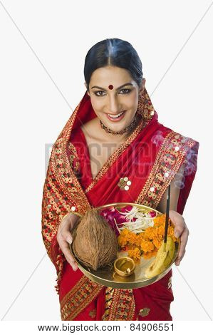 Woman in traditional Assamese mekhla holding religious offering poster
