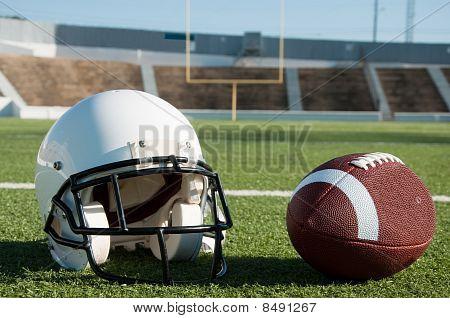 American Football And Helmet On Field