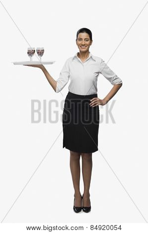 Air hostess carrying a tray of wine glasses