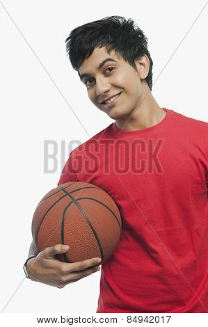 Portrait of a man holding a basket ball and smiling