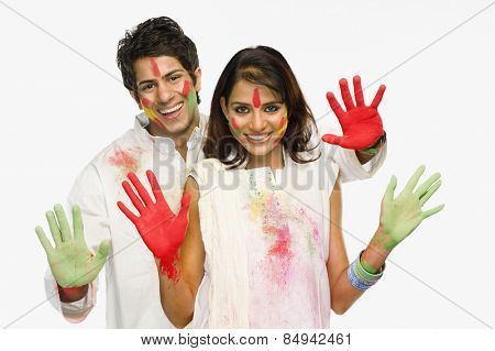 Couple showing their colored hands on Holi