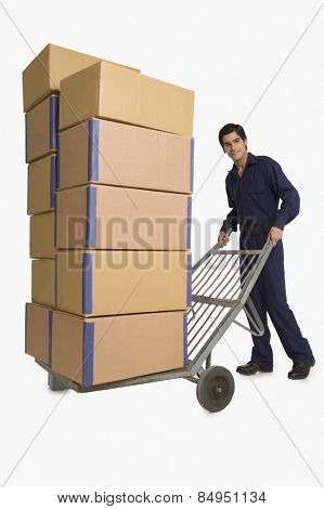 Storekeeper carrying cardboard boxes on hand truck