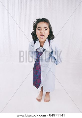 Portrait of a girl wearing oversize shirt with tie and sticking her tongue out