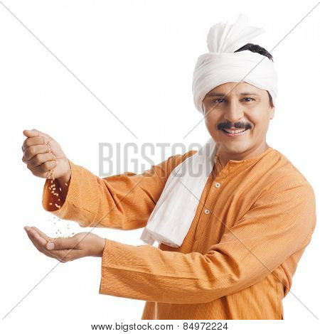 Portrait of a farmer holding wheat in his hand and smiling