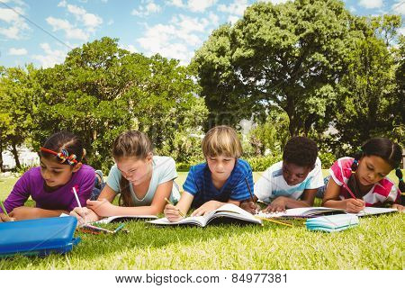 Portrait of children doing homework at the park