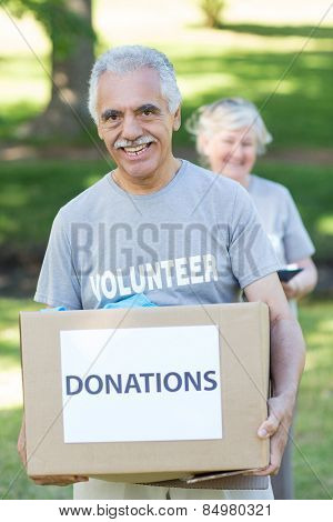 Happy volunteer senior holding donation box on a sunny day