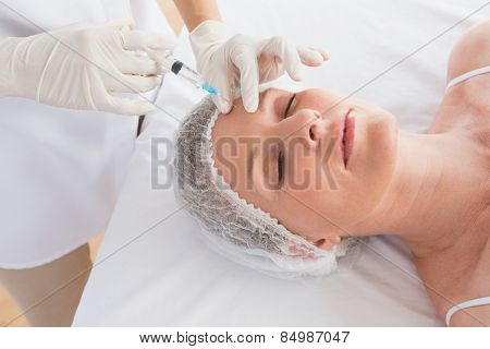 Woman receiving botox injection on her forehead in medical office poster
