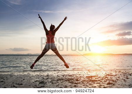 Sporty Woman Jumping On Sunset At The Beach.