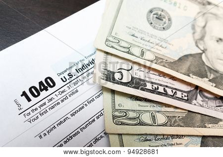 American dollar bills and 1040 tax form