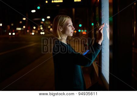 Female doing internet money payment with automated teller machine while standing in night city